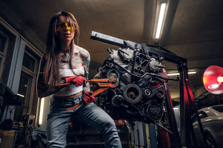 Female car mechanic holding a big hammer and working with a car engine suspended on a hydraulic hoist in the workshop.