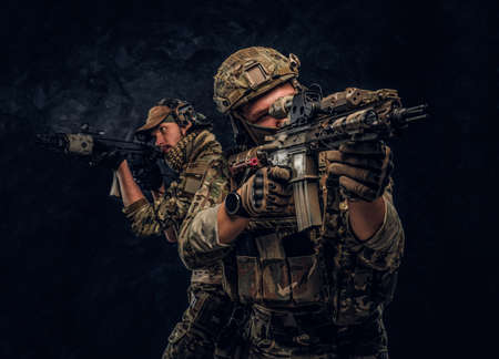 Two special forces soldiers in full protective equipment holding assault rifles and aiming at the targets. Studio photo against a dark wall.