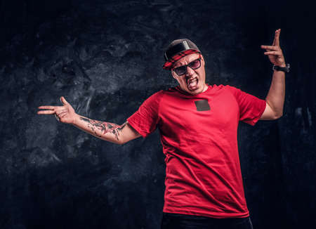 Stylish man with a tattoo on his hand dressed in a hip-hop style, having fun and posing for a camera. Studio photo against a dark textured wall Stock Photo