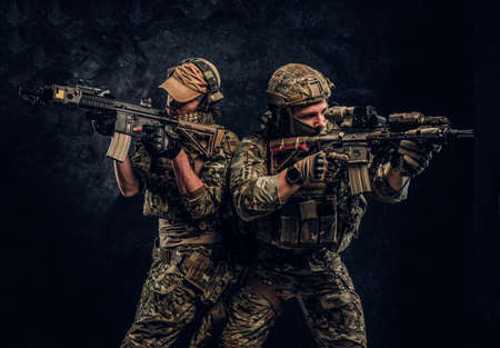 Private security service contractors, the elite special unit, full protective soldiers aiming at the targets. Studio photo against a dark wall.