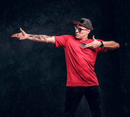 Stylish man with a tattoo on his hand dressed in a hip-hop style, posing for a camera. Studio photo against a dark textured wall