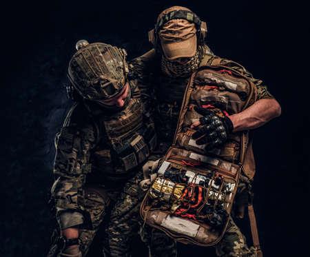Kampfkonflikt, Sondermission, Rückzug. Der Militärarzt rettet seinen verwundeten Teamkollegen und trägt ihn vom Schlachtfeld. Studiofoto gegen eine dunkle Wand