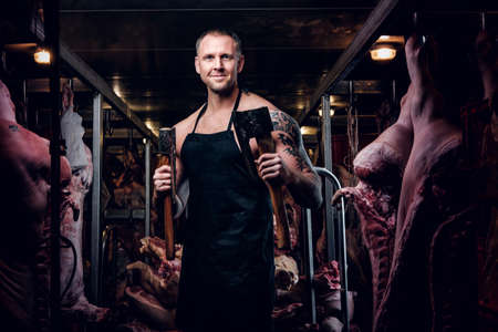 Smiling butcher with a tattoo on his hand wearing apron posing with two axes in a refrigerated warehouse in the midst of meat carcasses