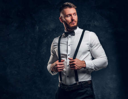 Old-fashioned young man in shirt with bow tie and suspenders. Studio photo against a dark wall background Stockfoto