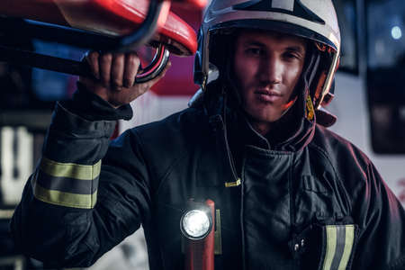 Close-up portrait of a handsome fireman wearing a protective uniform with flashlight included standing in a fire station garage