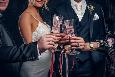 Close-up of bride and groom clinking champagne glasses at a wedding party. Studio shot Фото со стока