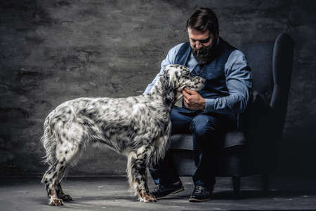 Bearded hunter wearing elegant clothes sitting on a sofa with his white English setter. Studio photo against a dark textured wall