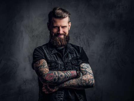 Portrait d'un homme tatoué avec barbe et coiffure posant les bras croisés. Photo de studio contre un mur sombre