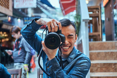 Hombres asiáticos jóvenes casuales están haciendo una foto con una cámara de fotos afuera en un lugar público. El está sonriendo. El hombre lleva chaqueta vaquera.