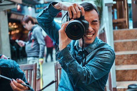 Casual young asian men is making a photo with photo camera outside in public place. He is smiling. Man is wearing denim jacket. Foto de archivo