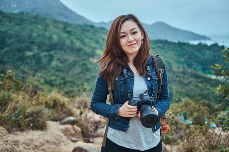 Portrait of a young smiling chinese woman with photo camera in hands. She enjoy beautiful sights of nature.