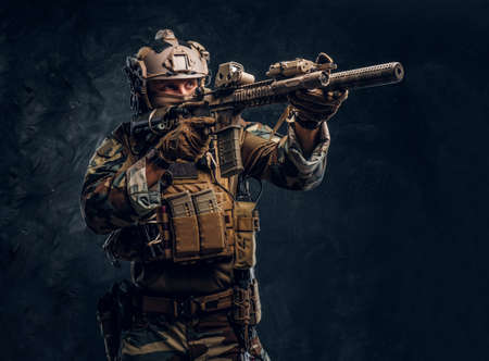 Elite unit, special forces soldier in camouflage uniform holding assault rifle and aiming with optical sight. Studio photo against a dark textured wall