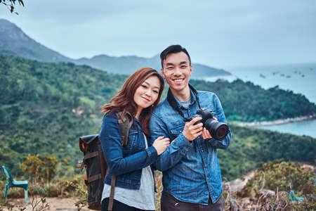 Linda pareja china romántica disfrutando de la hermosa naturaleza. El hombre tiene una cámara de fotos. Tienen camisas de mezclilla y estilo casual.