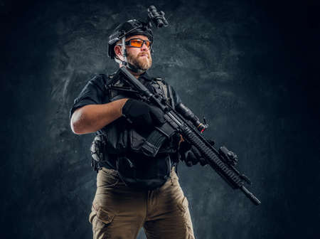 Bärtiger Soldat der Spezialeinheiten, der Körperpanzerung und Helm mit Nachtsicht trägt und ein Sturmgewehr hält. Studiofoto gegen eine dunkle strukturierte Wand