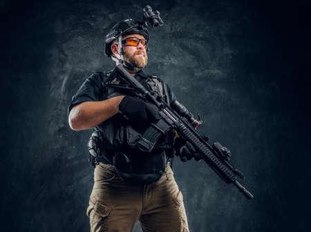 Soldato barbuto delle forze speciali che indossa armatura e casco con visione notturna che tiene in mano un fucile d'assalto. Foto in studio contro una parete con texture scura