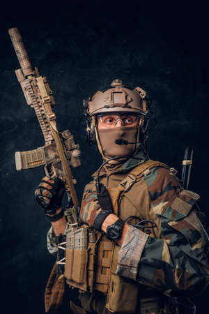 Private security service contractor in camouflage uniform posing with assault rifle. Studio photo against a dark textured wall