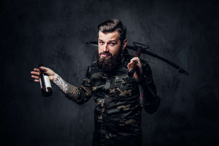 Stylish bearded hipster man in military shirt holding a craft beer and a medieval crossbow. Studio photo against a dark wall