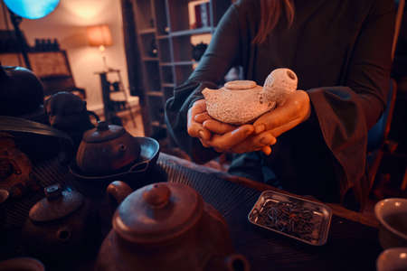 Chinese tea ceremony. Oriental master wearing a gray dress holding a teapot in the dark room with a wooden interior. Tradition, health, harmony