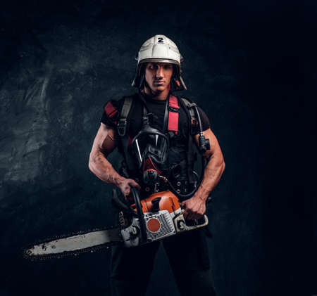 Attractive young handyman in helmet is looking forward. He holds chainsaw in hands. Man has oxygen mask on his chest. Dark background.
