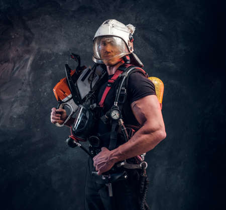 Muscular worker with chainsaw on his shoulder. He wear helmet with protective glass and looking to the camera. Its oxygen mask on his neck. Dark background.