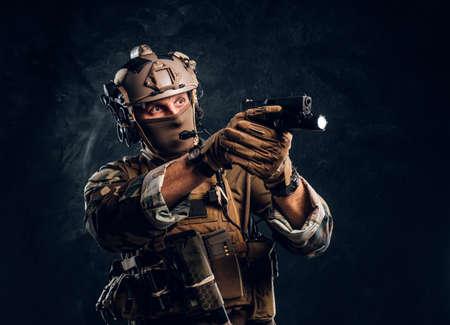Unidad de élite, soldado de las fuerzas especiales con uniforme de camuflaje que sostiene un arma con una linterna y apunta al objetivo. Foto de estudio contra una pared con textura oscura