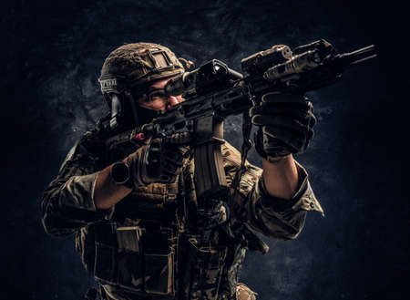 Close-up studio photo against a dark textured wall. The elite unit, special forces soldier in camouflage uniform holding an assault rifle with a laser sight and aims at the target Imagens