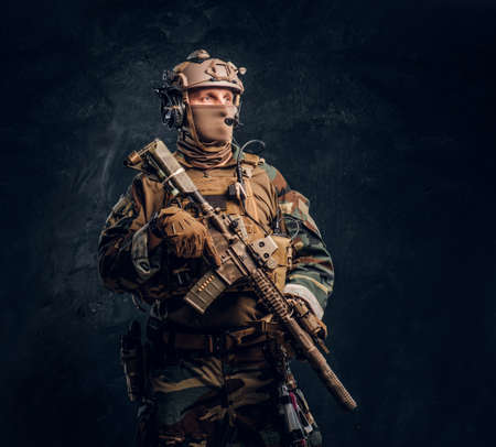 Elite unit, special forces soldier in camouflage uniform posing with assault rifle. Studio photo against a dark textured wall