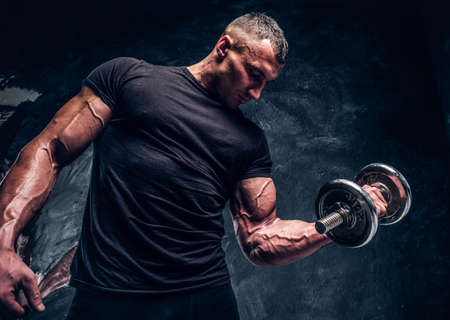 Bodybuilder in black t-shirt is lifting a dumbbell with effort. There is dark background.