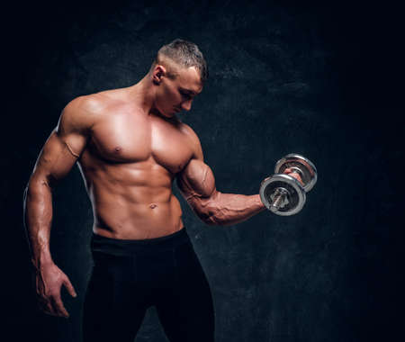 Shirtless youg male is looking on his muscules while holding a dumbbell. There are dark background.