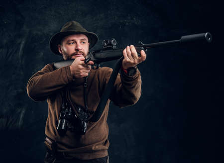 Male hunter holding a rifle and aiming at his target or prey. Studio photo against dark wall background