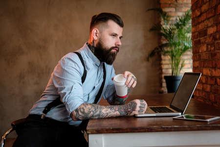 Nachdenklicher Geschäftsmann lehnt sich auf den Tisch. Er trägt Hemd und Hosenträger. Er hat Tätowierungen an Armen und Hals. Mann arbeitet an seinem Laptop. Büro im Hintergrund.