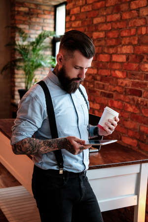 Imposing bearded man is standing next to the table. He is wearing shirt and suspender. He has tattoes on his arms and neck. He is holding tablet and cup of coffee. Man is reading.