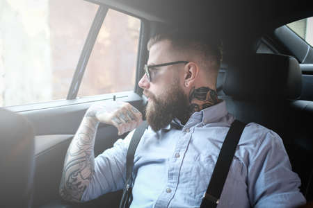 Imposing bearded man in sunglasses is sitting in the car. He is wearing shirt and suspender. He has tattoes on his arm and neck. He is looking to the window.