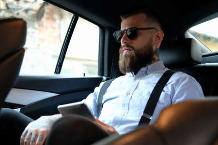 Serious bearded man in sunglasses is sitting in the car. He is wearing shirt and suspender. He has tattoes on his hand and neck. He is holding a tablet. Stock Photo