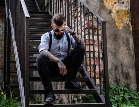 Smart bearded man is sitting on the stairs. He is wearing shirt, suspender and sunglasses. He has tattoes on his arms. There are grass, brick wall and car at the background.