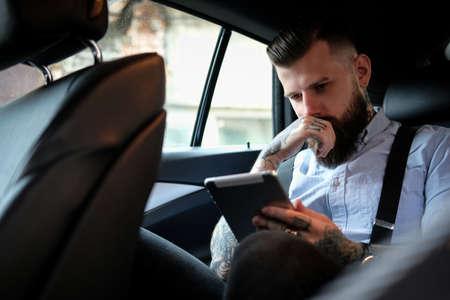 Nachdenklicher bärtiger Mann sitzt im Auto. Er trägt Hemd und Hosenträger. Er hat Tätowierungen an Armen und Hals. Mann liest etwas auf einem Tablet.