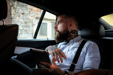 Self-confident bearded man is sitting in the car. He is wearing shirt and suspender. He has tattoes on his arms and neck. Man is holding a tablet and looking to the window. Stockfoto