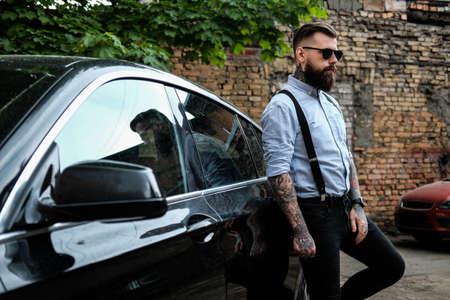 Intelligenter bärtiger Mann lehnt sich an sein Auto. Er trägt Hemd, Hosenträger und Sonnenbrille. Er hat Tattoos und Uhr auf seinen Armen. Es gibt Slum und Baum im Hintergrund.