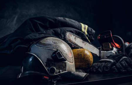 Sicherheitsausrüstung - Jacke, Helm, Sauerstoffflasche und Kettensäge auf dem Tisch. Es gibt einen dunklen Hintergrund. Dunkles Foto.