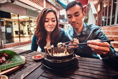 Happy young chinese couple sitting at cafe outside enjoying traditional asian food. Widescreen shooting.