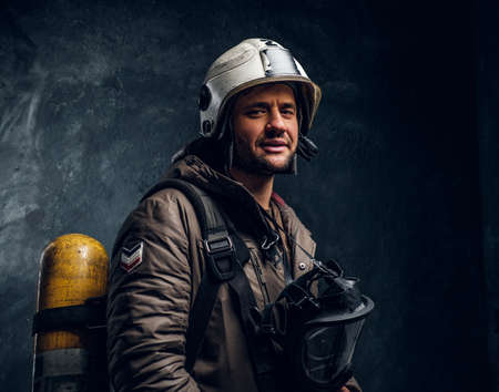 Smiling lifeguard with helmet and oxygen mask after long working day. There are dark background.