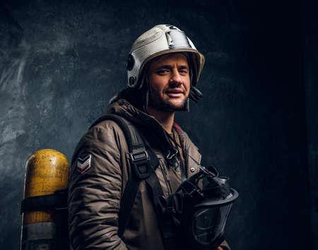 Uśmiechnięty ratownik z kaskiem i maską tlenową po długim dniu pracy. Jest ciemne tło.