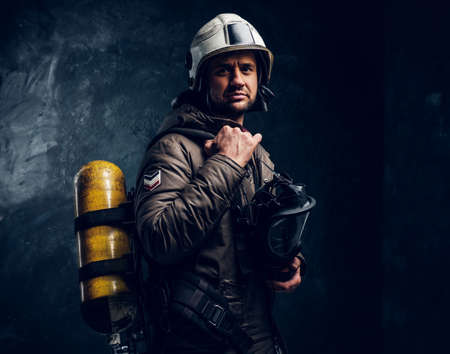 Portrait of brave lifeguard with helmet and oxygen mask in hand. Dark background. Stockfoto