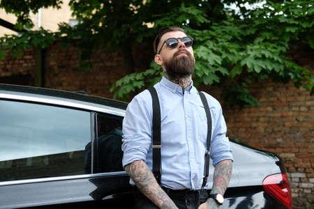 L'homme barbu pensif s'appuie sur sa voiture. Il porte une chemise, des bretelles et des lunettes de soleil. Il a des tatouages et regarde sur ses bras. Il y a une cour et des arbres à l'arrière-plan.