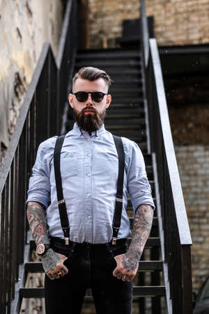 Serious bearded man is standing near stairs. He is wearing shirt, suspender and sunglasses. He has tattoes on his arms and neck. Man put his fists on the pockets.