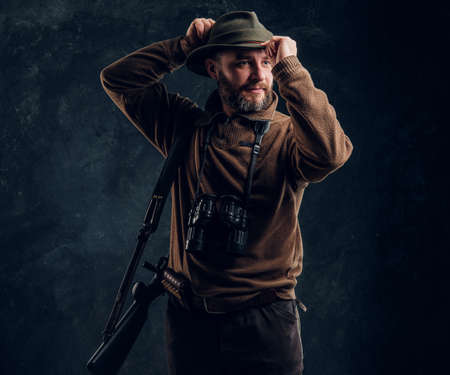 Bearded hunter with rifle and binoculars corrects his hat and looking sideways. Studio photo against dark wall background