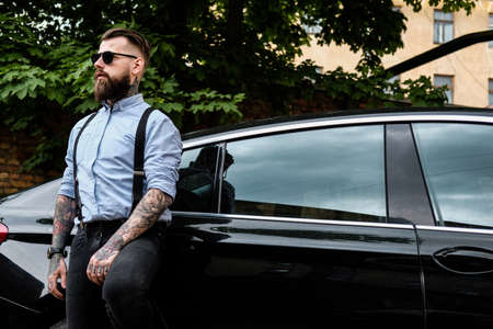 Pensive bearded man is leaning on his car. He is wearing shirt, suspender and sunglasses. He has tattoes and watch on his arms. There are building and trees at the background. Stock Photo