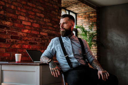 Imposing bearded man is leaning on the table. He is wearing shirt and suspender. He has tattoes on his arms.There are laptop and cup of coffee at the background.