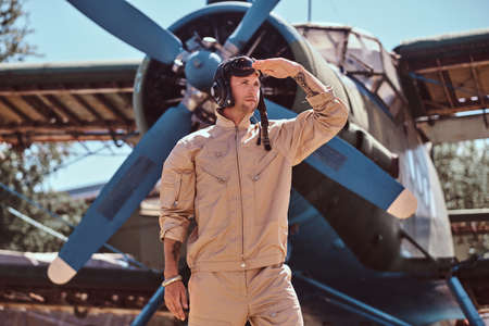 Military pilot is thoughtfully looks away. He is standing near small blue retro jet, just near propeller. He is covering ees with hand from the sun. 免版税图像