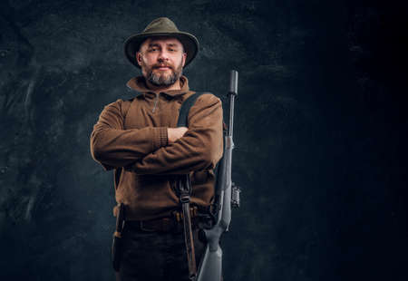 Portrait of a bearded hunter with rifle posing with his arms crossed, looking at a camera. Studio photo against a dark wall background